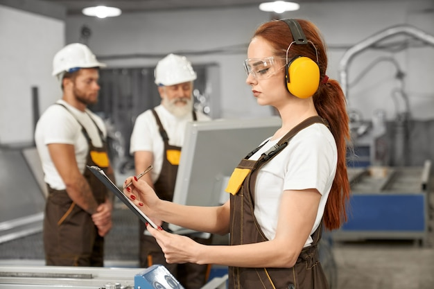 Engenheiros que trabalham com cortador a laser de plasma na fábrica. Foto gratuita