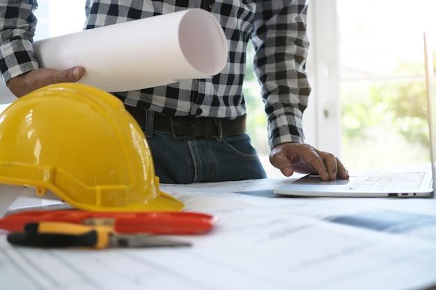 Engenheiros trabalham com laptops e blueprints Foto Premium