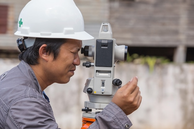 Engenheiros usam tacheometer ou teodolito para colunas de linha de pesquisa para a construção Foto Premium