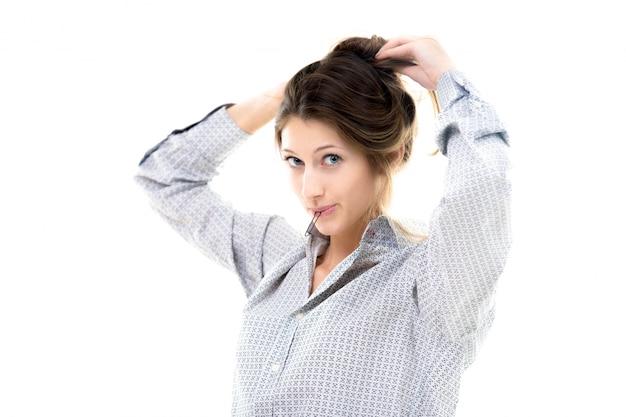 Engraçada bela garota com hairpin em seus lábios reunindo cabelos em um coque Foto gratuita
