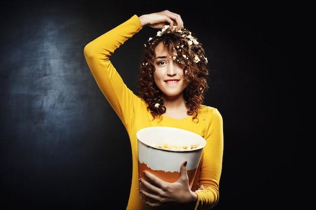Engraçadinha, comendo pipoca enquanto assiste a shows em casa Foto gratuita