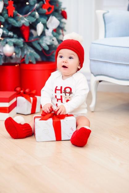 Engraçado bebê infantil menina descompacta caixa de presente de natal. feliz natal e feliz ano novo. Foto Premium