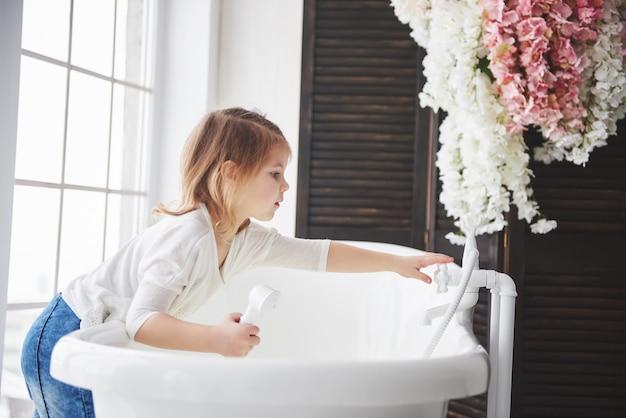 Engraçado bebê menina com cabelos cacheados. prepare-se para tomar um banho. banheiro iluminado espaçoso. o conceito de um corpo saudável e limpo. cuidar de si mesmo desde a infância Foto Premium