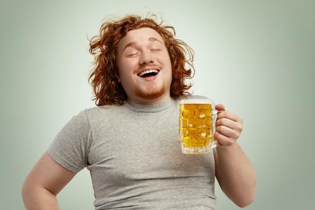 Engraçado caucasiano jovem macho se sentindo feliz e relaxado, antecipando cerveja gelada fresca em suas mãos após um árduo dia de trabalho, fechando os olhos de gozo. homem ruivo com excesso de peso barbudo bebendo cerveja Foto gratuita
