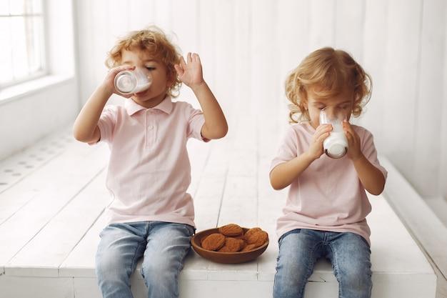 Engraçado crianças comendo biscoitos e bebendo leite Foto gratuita