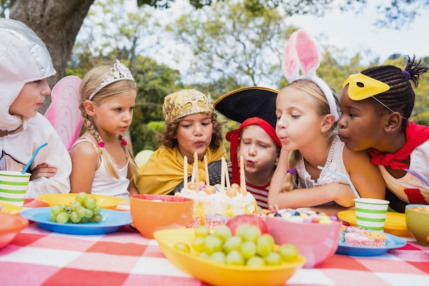 Engraçado crianças soprando juntos na vela durante uma festa de aniversário Foto Premium