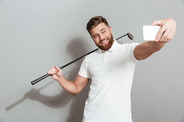 Engraçado feliz golfista fazendo selfie em seu smartphone Foto gratuita