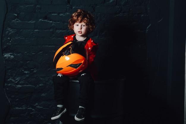 Engraçado garoto encaracolado segurando um capacete nas mãos Foto Premium