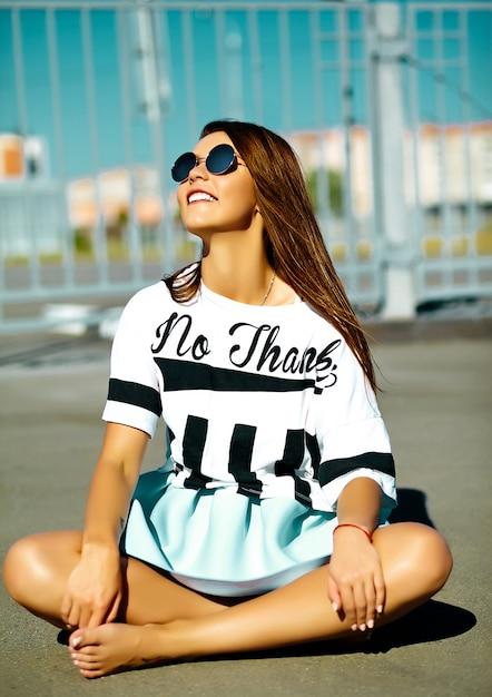 Engraçado glamour louco elegante sexy sorridente mulher jovem e bonita modelo em pano brilhante de verão hipster casual sentado na rua atrás do céu azul Foto gratuita