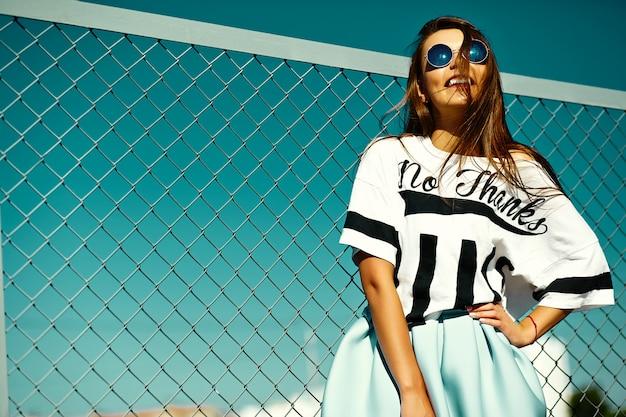 Engraçado glamour louco elegante sexy sorridente mulher jovem e bonita modelo em roupas casuais de verão hipster brilhante na rua atrás do céu azul Foto gratuita