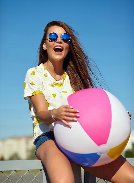 Engraçado glamour louco elegante sorridente modelo mulher jovem e bonita em roupas casuais de verão hipster brilhante posando na rua atrás do céu azul e sentado em cima da muro. brincando com b inflável colorido Foto gratuita