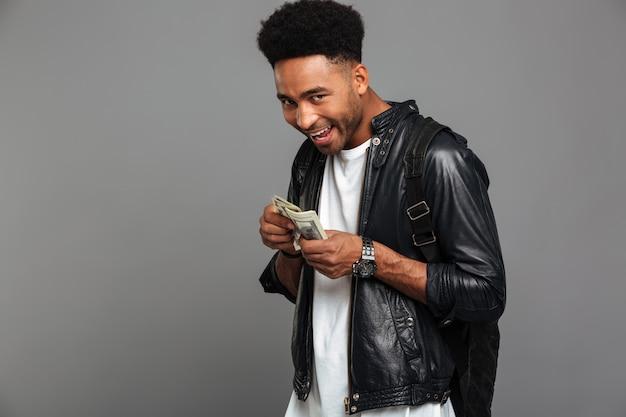 Engraçado homem africano com corte de cabelo à moda considera avidamente dinheiro, olhando Foto gratuita
