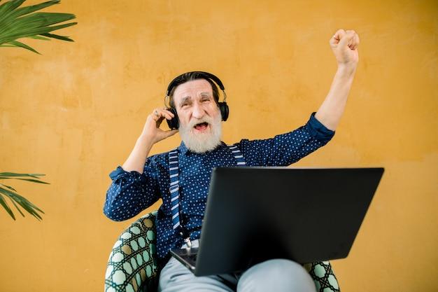 Engraçado homem barbudo alegre com fones de ouvido sentado na cadeira no fundo da parede amarela e usando o computador portátil Foto Premium