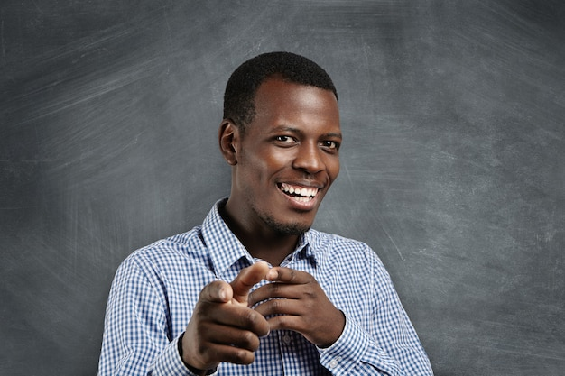 Engraçado jovem cliente africano sorrindo alegremente e apontando os dedos como se estivesse escolhendo você e convidando para uma grande venda. emoções positivas, expressões faciais, sentimentos. foco seletivo Foto gratuita
