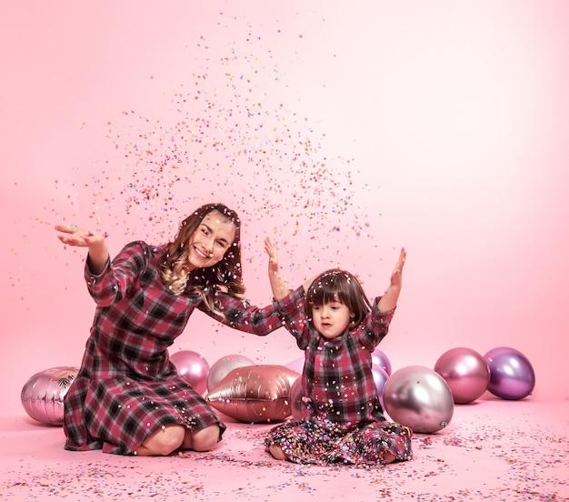 Engraçado mãe e criança sentada em um fundo rosa. menina e mãe se divertindo com balões e confetes Foto gratuita