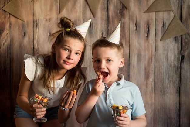 Engraçado menino e menina comendo pipoca, rindo de uma festa. fundo de madeira com bandeiras, festa de aniversário alegre Foto Premium