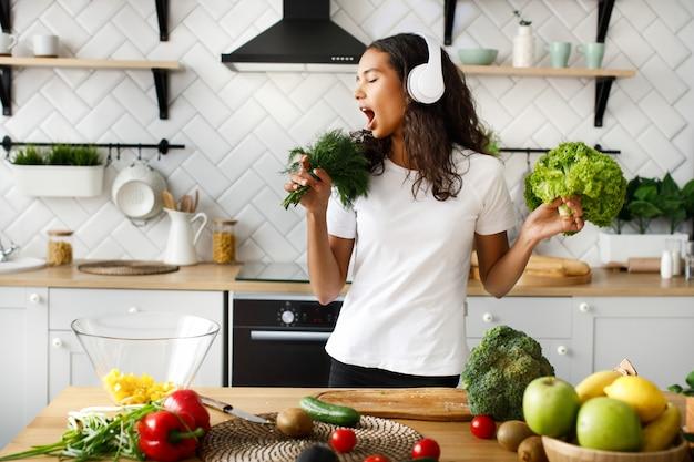 Engraçado mulata em grandes fones de ouvido sem fio está cantando no microfone de vegetação imaginária na cozinha moderna perto da mesa cheia de legumes e frutas Foto gratuita