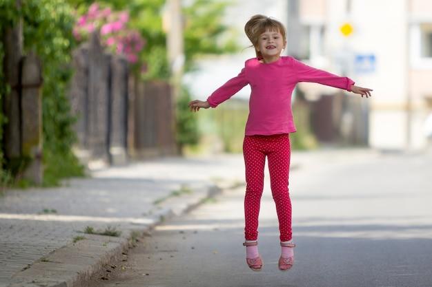 Engraçado pequena garota desdentada engraçada sorridente em roupas casuais rosa com salto de pônei loiro comprido Foto Premium