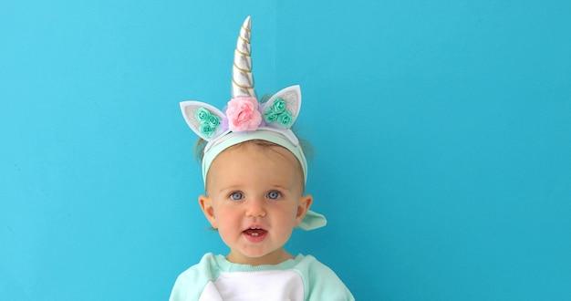 Engraçado unicórnio menina em fundo azul Foto Premium