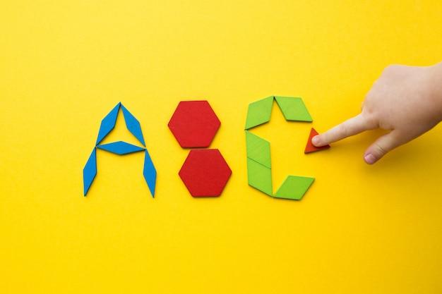 Enigma de madeira tangram de cor no alfabeto forma de letras de abc no fundo amarelo com a mão de uma criança Foto Premium