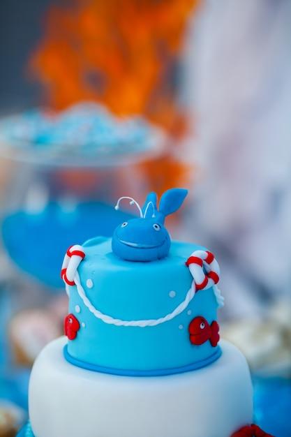 Enorme bolo de aniversário azul e branco com doce caranguejo, peixe, estrelas do mar e baleia engraçada no topo Foto Premium