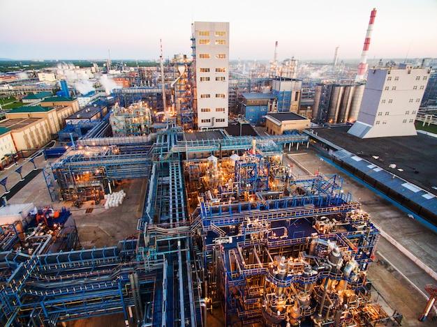 Enorme refinaria de petróleo com estruturas metálicas, tubulações e destilação do complexo com luzes acesas ao entardecer. vista aérea Foto Premium