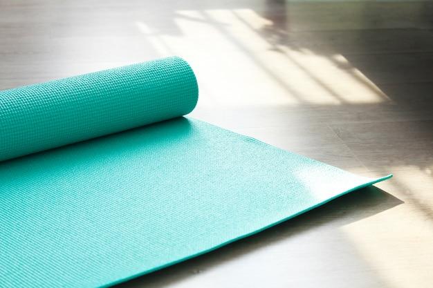 Enrolado de yoga ou pilates esteira para exercício no piso de madeira natural, classe de esporte Foto Premium