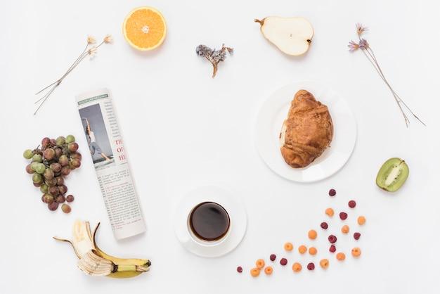 Enrolado jornal com xícara de café; croissant e frutas no fundo branco Foto gratuita
