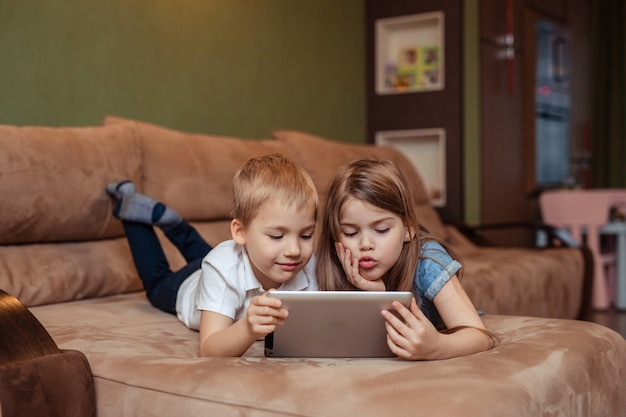 Ensino a distância em casa. gêmeos irmão e irmã estão estudando em casa usando um tablet. eles estão felizes e rindo enquanto está deitado no sofá Foto Premium