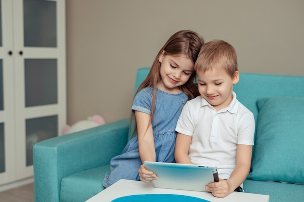 Ensino a distância em casa. gêmeos irmão e irmã estudam em casa usando tablet Foto Premium