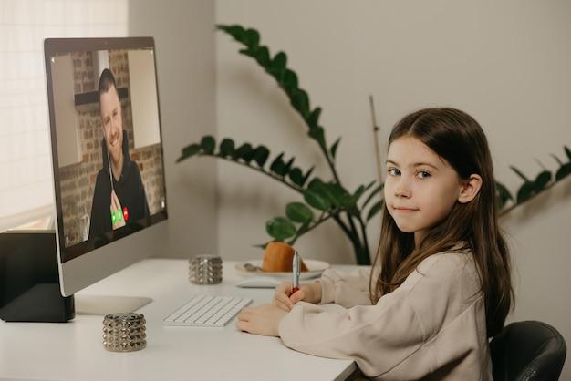 Ensino à distância. uma jovem garota com cabelos longos, estudando remotamente de sua professora on-line. uma criança bonita aprende uma lição usando um computador desktop em casa. educação em casa. Foto Premium