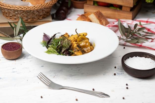 Ensopado de legumes com carne, pedaços de milho, pimenta e legumes, manjericão, salsa em chapa branca. Foto gratuita