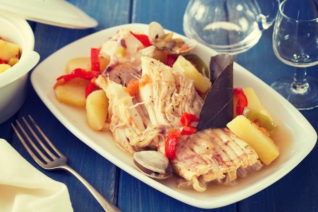 Ensopado de peixe no prato branco com vinho na superfície de madeira azul Foto Premium
