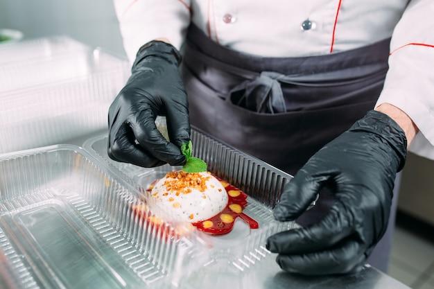 Entrega de comida no restaurante. o chef prepara a comida no restaurante e a embala em pratos descartáveis. Foto Premium