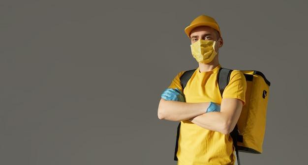 Entrega segura de alimentos. o correio em uniforme amarelo, máscara protetora e luvas fornece comida para viagem durante a quarentena de coronovírus. copie o espaço para texto Foto Premium