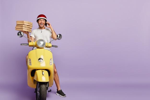 Entregador amigável dirigindo scooter segurando caixas de pizza Foto gratuita