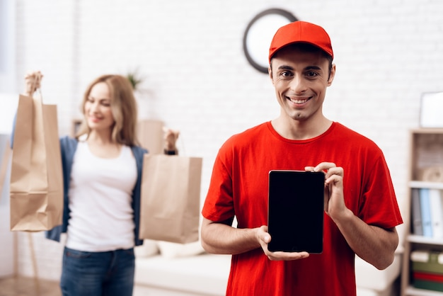Entregador árabe com tablet e menina com packege Foto Premium