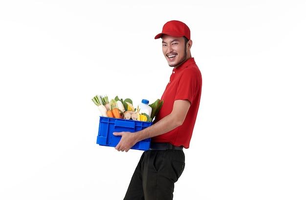 Entregador asiático vestindo uniforme vermelho, segurando uma cesta de alimentos frescos, isolada sobre uma parede branca. Foto gratuita