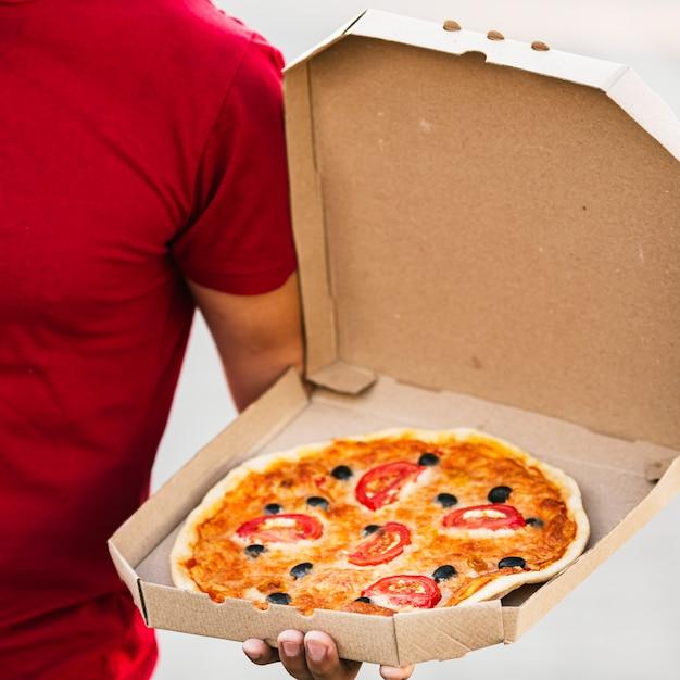 Entregador close-up, segurando, caixa pizza Foto gratuita