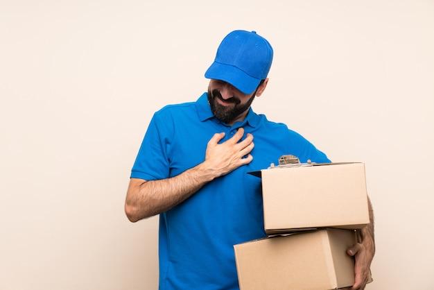 Entregador com barba sobre parede isolada, com uma dor no coração Foto Premium
