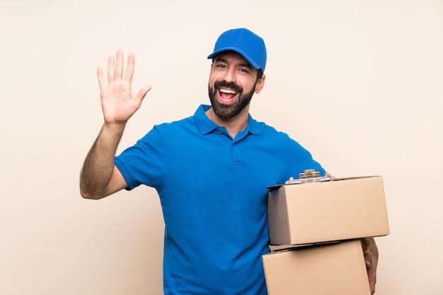 Entregador com barba sobre parede isolada saudando com mão com expressão feliz Foto Premium