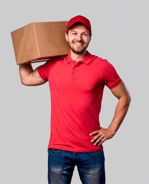 Entregador com pacote no ombro Foto gratuita