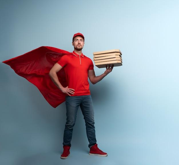 Entregador com pizzas age como um super-herói poderoso. conceito de sucesso e garantia na remessa. fundo ciano Foto Premium