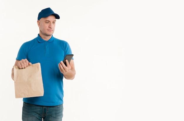 Entregador com saco de papel, olhando para smarthpone Foto gratuita