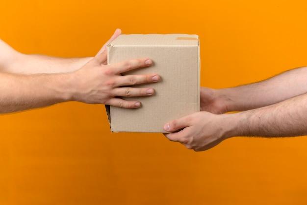 Entregador dando pacote de caixa para o cliente na vista lateral laranja isolada Foto gratuita