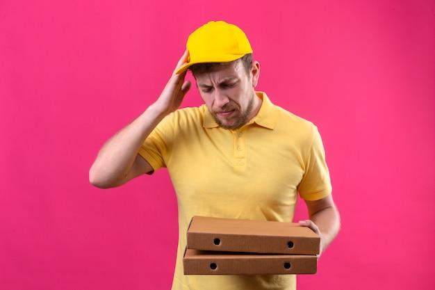 Entregador de camisa pólo amarela e boné segurando caixas de pizza em pé com a mão na cabeça por engano, lembre-se do erro, esqueci o conceito de memória ruim no rosa isolado Foto gratuita