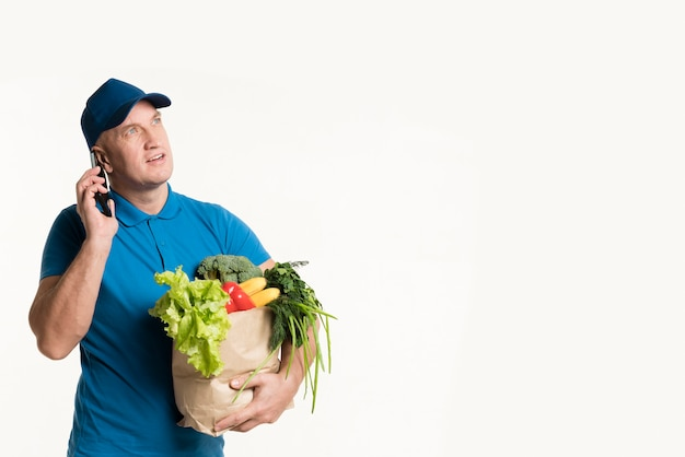 Entregador de telefone com sacola de compras na mão Foto gratuita