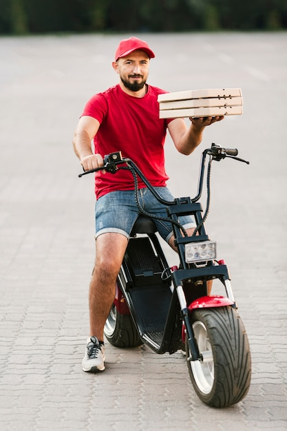 Entregador de tiro cheio segurando caixas de pizza Foto gratuita