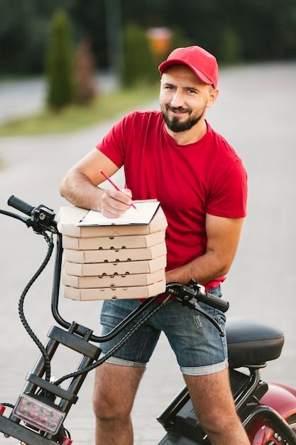 Entregador de tiro médio com moto e pizza Foto gratuita