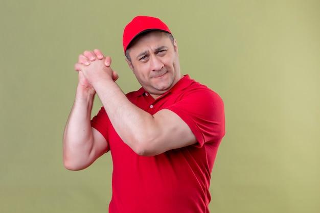 Entregador de uniforme vermelho e boné em pé com um gesto de trabalho em equipe sorrindo confiante sobre o espaço verde isolado Foto gratuita
